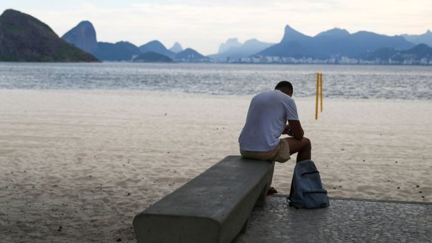 Hombre sentado en la playa de Icarai, Brasil