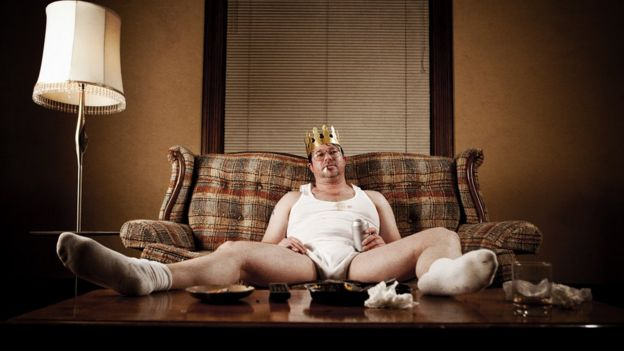 Hombre en sofá con corona de rey en ropa interior