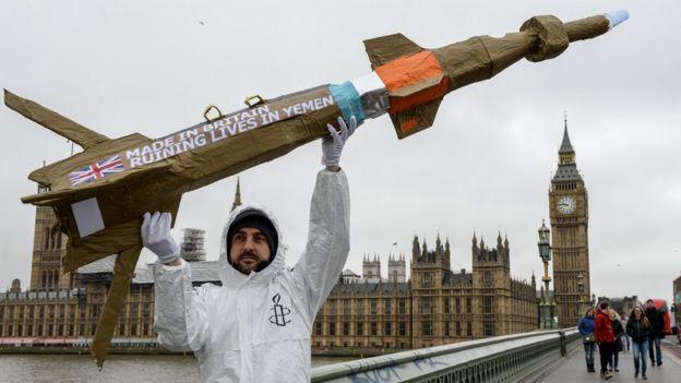 یک عضو عفو بینالمللی در حال اعتراض به فروش تسلیحات بریتانیا به یمن در نزدیکی پارلمان بریتانیا