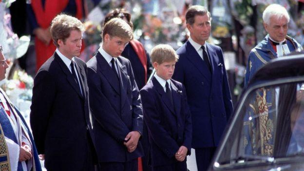 El príncipe Harry, entre su padre, el príncipe Carlos, y su hermano, el príncipe William, viendo pasar el coche fúnebre con los restos de su madre.