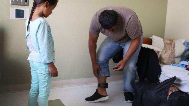 Una niña ve cómo su padre se pone una tobillera electrónica, requisito de las autoridades migratorias