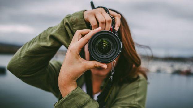 Mujer tomando una foto con la cámara réflex.