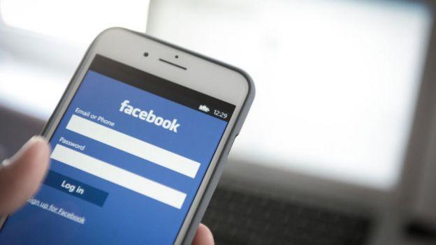 Pantalla de celular con la página de inicio de Facebook.
