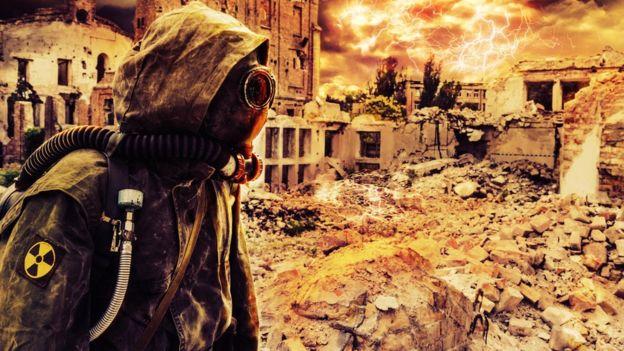 Ilustração mostra pessoa usando roupa de proteção em ambiente devastado por guerra nuclear
