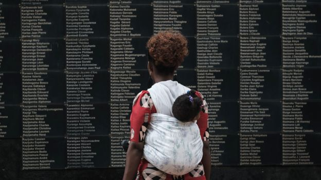 Una mujer cargando a su hijo mira una pared con los nombres de las víctimas del genocidio de 1994, en el Memorial del Genocidio en Kigali.