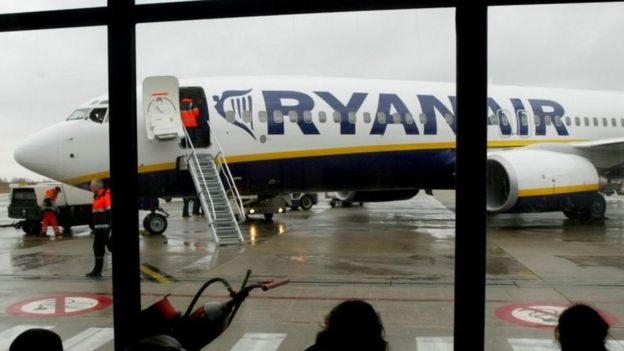 Travellers wait in front of a passenger jet belonging to Ryanair