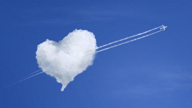 Imagen de una nube en forma de corazón y un avión atravesándola.