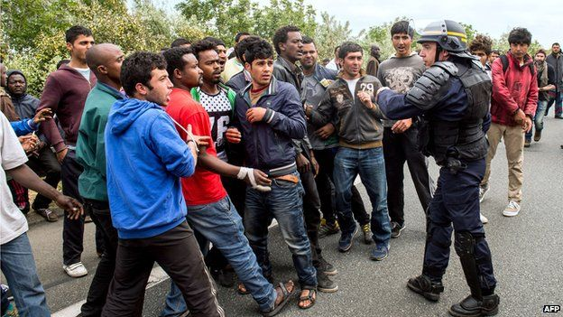 French riot police officer stands as illegal migrants wait to board lorries
