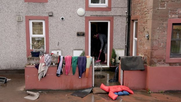 A man cleaning up after his house was flooded