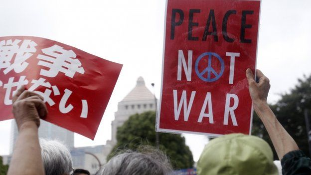 Protesters holding anti-war placards