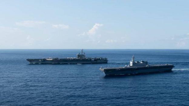Tàu USS Ronald Reagan (xa, bên trái) đi cùng với tàu sân bay trở trực thăng Izumo của Lực lượng phòng vệ hàng hải Nhật Bản