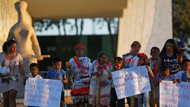 Integrantes do povo Guarani Kaiowa seguram cartazes de protesto em frente a estátua que representa a Justiça em Brasília