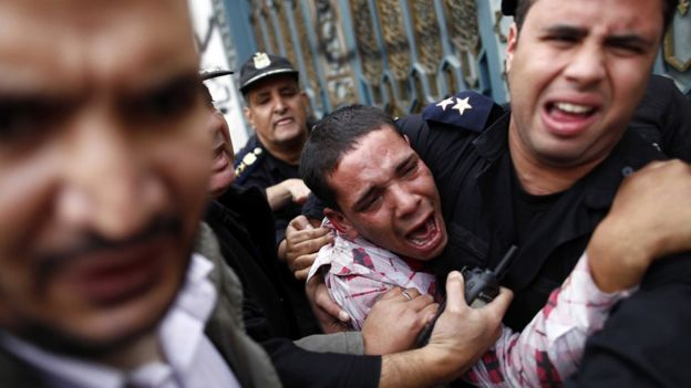 Egyptian policemen protect an opposition supporter during clashes with Muslim Brotherhood supporters outside the Ittihadiya presidential palace in Cairo (5 December 2012)