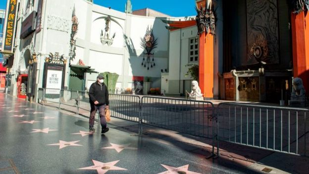 Un hombre camina por un desértico Paseo de la Fama de Hollywood.