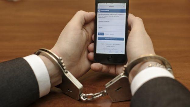 Una foto de unas manos esposadas sujetando un tel??fono en el que se puede ver la red social VK.