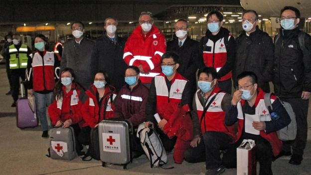 "Chinese medics posing for a group photo after landing on a China Eastern flight on March 13 at Rome""s Fiumicino international airport from Shanghai, bringing medical aid to help fight the new coronavirus in Italy"