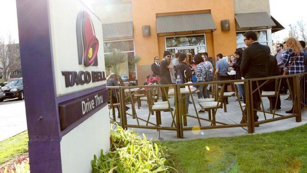 الزبائن يقفون أمام مطعم تاكو للوجبات السريعة