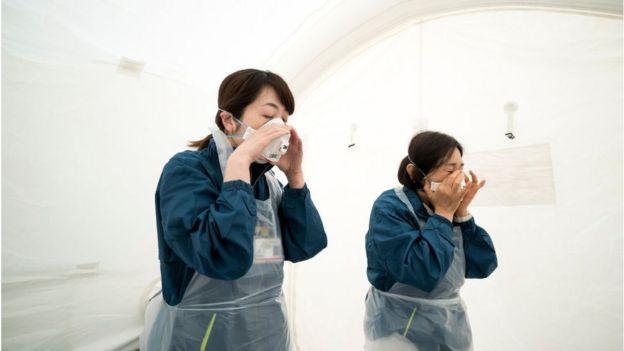 日本东京医务人员准备防护装备,准备对潜在的新冠病毒患者进行筛查。