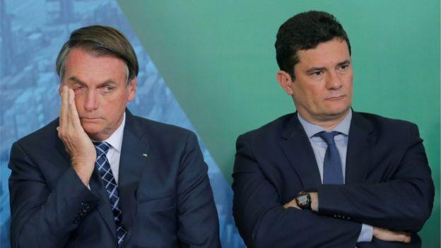 Bolsonaro e Moro sentados em evento, olhando para sentidos opostos