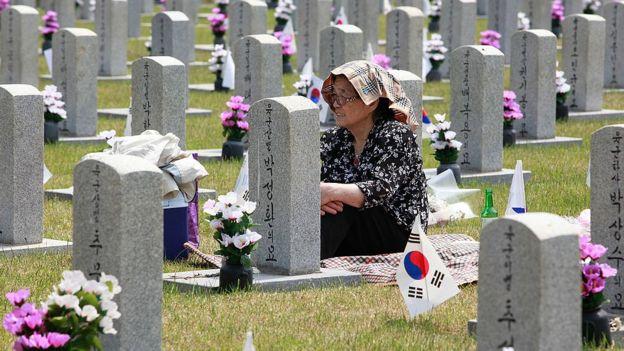 Mujer frente a la tumba de un familiar de la guerra.
