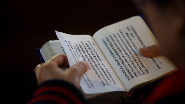 "A believer reads the bible during mass at St. Joseph""s Church, a government-sanctioned Catholic church, in Beijing, China, October 1, 2018. REUTERS/Thomas Peter"