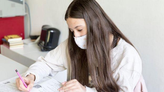 Niña con mascarilla haciendo la tarea