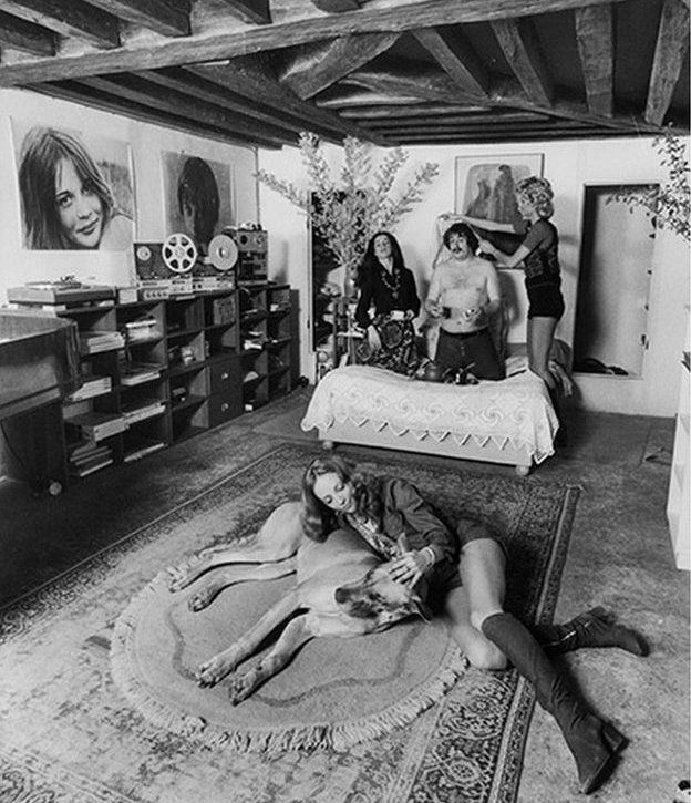 A woman and dog sitting on a rug, and a bare-chested man and two women on a bed
