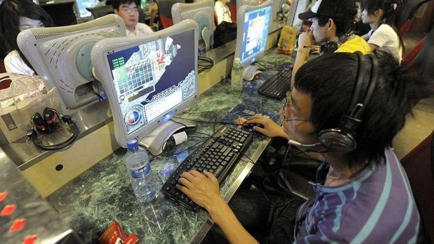 Un joven usa una computadora en un cibercafé.