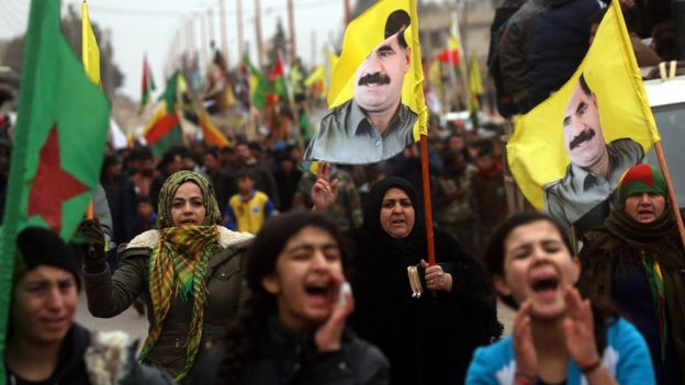 Syrian Kurds carry portraits of jailed PKK leader Abdullah Ocalan and YPG flags as they protest in support of Afrin in the Syrian town of Jawadiyah (18 January 2018)