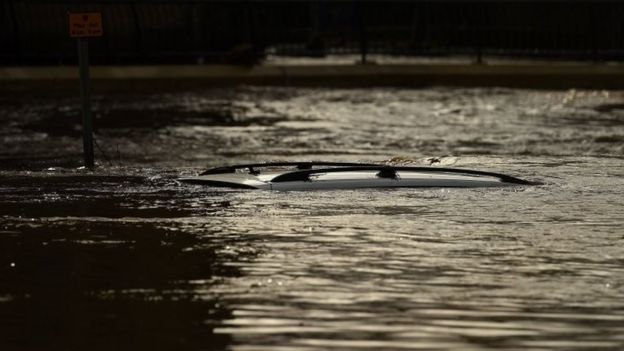 The roof of a submerged car is pictured in a flooded street in Mytholmroyd, northern England