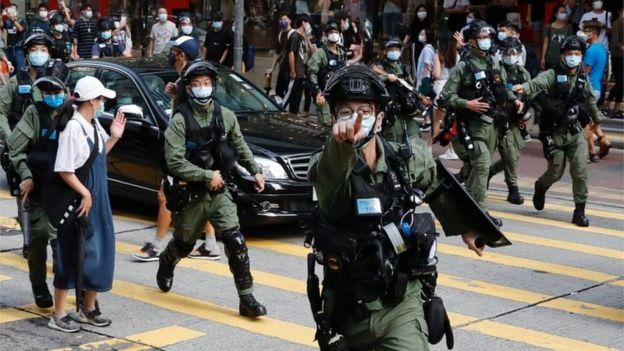 警方驱散马路上的群众。