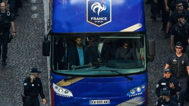 Elysée Chief Security Officer Alexandre Benalla is seen in the driver cabin (front L) of the bus carrying France's team players as they arrive on the Champs-Elysees avenue in Paris, on July 16, 2018