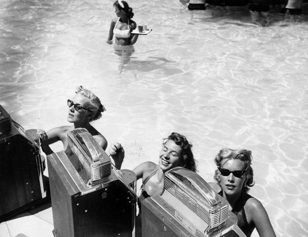 Tres mujeres jugando en máquinas tragamonedas en la piscina