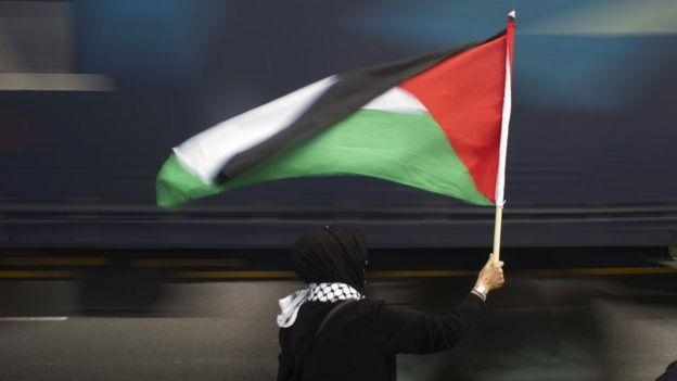 امرأة تحمل علم فلسطين