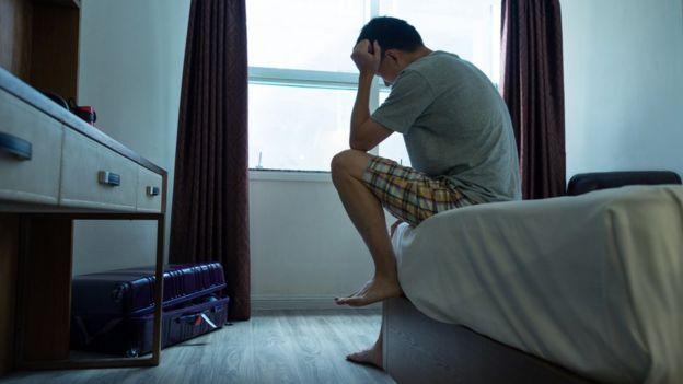 Homem triste sentado sobre a cama