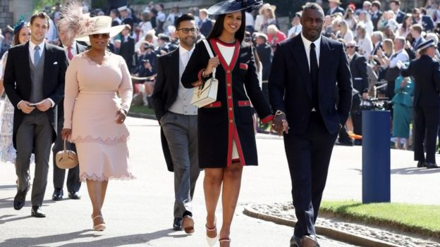 US TV star Oprah Winfrey, wearing pink, and British actor Idris Elba arrive at the chapel