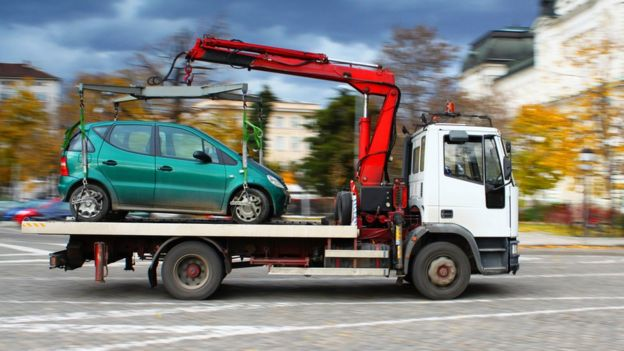 grúa llevándose un vehículo.