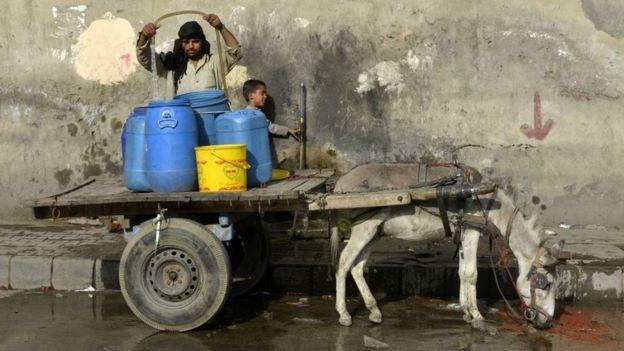 Um homem enche recipientes de plástico com água em um carrinho puxado por um burro