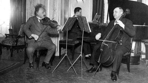 Einstein sentado tocando violino junto com outros músicos