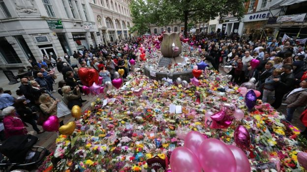 People leaving flowers in Manchester city centre one week after the Manchester Arena attack