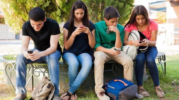 Un grupo de adolescente mirando sus pantallas en lugar de hablar entre ellos.
