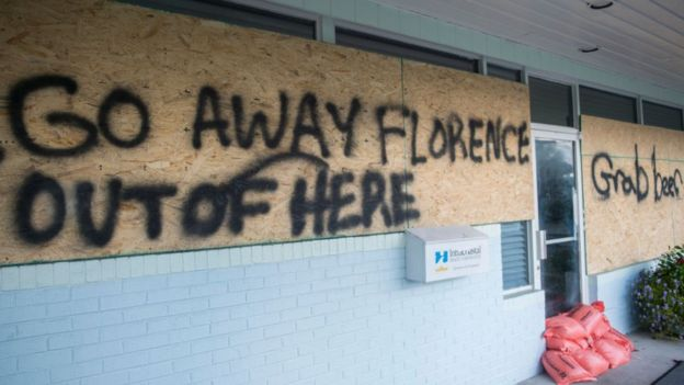 "a sign tells the hurricane to ""go away"""