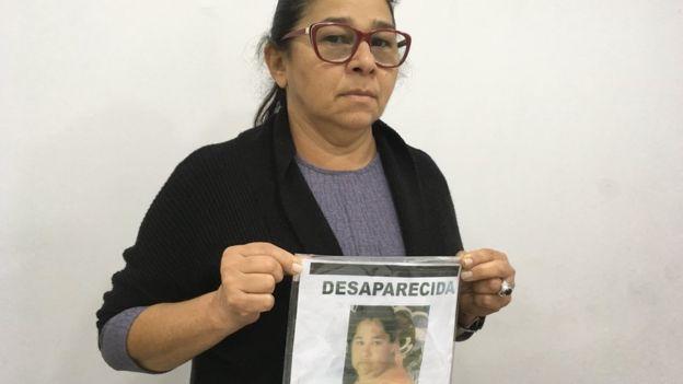 Marta Torres Castelo Branco segura cartaz com a foto da filha Eliene, que desapareceu em 2013, com 36 anos.