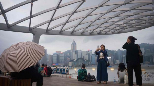 Khách du lịch chụp ảnh Cảng Victoria ở Hong Kong.