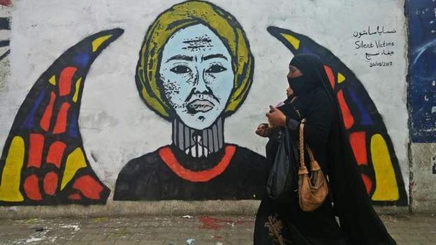 الجدارية تشرح معاناة أهالي المختفين قسريا وتصور امرأة في رقبتها قضبان خلفها شخص معتقل والقمرية-نافذة مستديرة زجاجها ملون- كناية عن اليمن حيث تعتبر علامة أساسية في العمارة اليمنية.