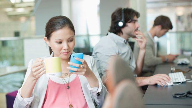 Mujer con una taza y mirando su celular
