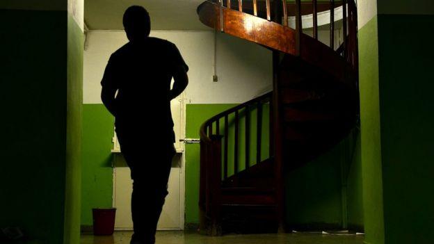 Sombra de um aluno em corredor de escola