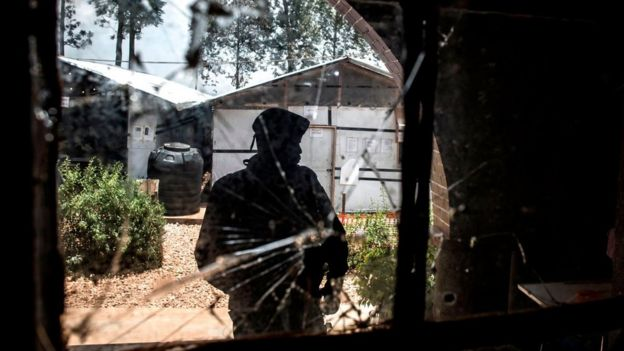 Un oficial de policía está de guardia frente a una ventana llena de agujeros de bala en un centro de tratamiento de ébola, que fue atacado el 9 de marzo de 2019 en Butembo.