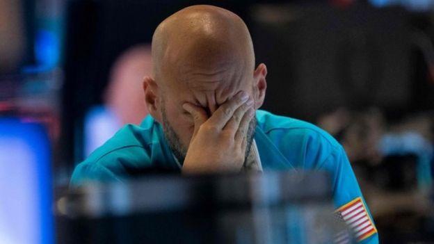 Un comerciante se limpia los ojos mientras mira los precios de las acciones en la Bolsa de Nueva York el 23 de agosto