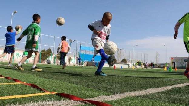 A boy juggles the ball on a football field